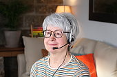 Senior woman using headset with microphone