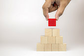 Hand picking a cube shape wooden block toy stacked in pyramid shape without graphics for Business design concept and activity for child foundation practice skills.