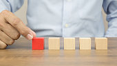 Close-up hand choose a cube wooden toy blocks stacked without graphics for Business design