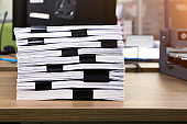 Close-up pile of a lots paper and paperwork report or printout document on office desk stack up