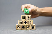 Close-up hand choose a wooden toy blocks with fire exit icon for fire safety protection concepts.