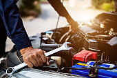 Auto mechanic hands using wrench to repair and checking a car engine systems. concepts of car insurance support and services.