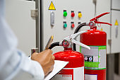 Engineer are inspection Fire extinguisher in fire control room for prevention, rescue and safety Concept.
