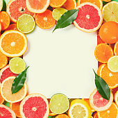Frame of citrus fruits like lime, lemon, orange and tangerine with orange tree leaves