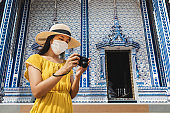 New normal travel of traveler asian woman with mask and camera sightseeing in temple Thailand