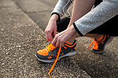 Woman runner tying shoelaces before jogging in autumn tree alley park