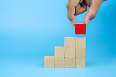 Hand picking a cube shape wooden block toy stacked in triangle shape without graphics for Business design concept and activity for child foundation practice skills.