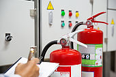 Engineer are checking and inspection a fire extinguishers in the fire control room for safety and prevention.