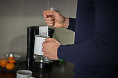 Man pouring boiling water from kettle to mug making tea