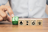 Close-up hand choose a wooden toy blocks stacked with fire exit icon