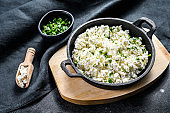 Cottage cheese in a cast-iron bowl with herbs. Organic dairy products. Black background. Top view