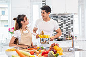 Happy Asian young married couple prepare for making spaghetti Bolognese in kitchen. Boyfriend and girlfriend cooking together. People lifestyle and romantic relationship concept. Valentines day indoor