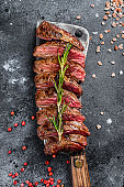 Grilled top blade, Denver steak. Marble meat beef. Black background. Top view