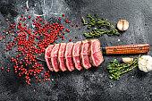 Sliced  Grilled Top Blade steak. Organic beef meat. Black background. Top view