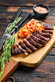 Grilled top sirloin cap or picanha steak on a cutting board with herbs. Dark wooden background. Top view