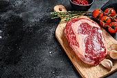 Raw fresh meat Ribeye Steak with seasoning on cutting board. Rib eye beef steak. black background. top view. Copy space