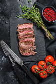 Grilled sliced skirt steak with seasonings and spices. Marbled meat. Black background. Top view