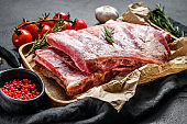 raw pork meat ribs with ingredients for cooking rosemary and garlic in a wooden bowl. Black background. Top view