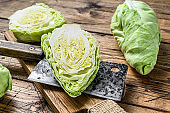 Raw Cutting Pointed white cabbage head on a cutting board. Wooden background. Top view
