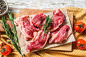 Strips of marbled beef, quick steak on cutting board. White wooden background. Top view