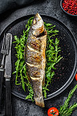 Baked sea Bass fish with arugula, grilled seabass. Black background. Top view