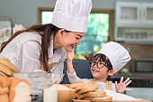 Cute little Asian boy painting beautiful woman face with dough flour. Chef team playing and baking bakery in kitchen funny. Homemade food and bread. Education and people lifestyles learning concept