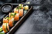 Philadelphia maki sushi with salmon, prawn, avocado, cream cheese. Sushi roll menu. Black background. Top view. Copy space