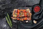 Bbq pork and beef kebab meat on wooden skewers.  Black background. Top view