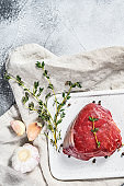 Marble beef tenderloin. Raw filet Mignon steak on a white chopping Board. Gray background. Top view