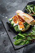 Baguette sandwich with goat cheese, pear marmalade, chard and spinach. Black background. Top view