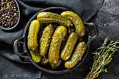 Marinated pickled cucumbers with herbs and spices. Black background. Top view