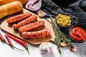 Ingredients for different homemade Hot Dogs, with fried onion, chili, tomatoes, ketchup, cucumbers, and sausage. White background. Top view