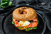 Smoked salmon bagel toasts with soft cheese, spinach and egg. Black background. Top view