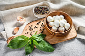 Mini mozzarella cheese in a wooden bowl with Basil leaves. gray background. Top view