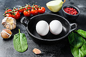 Ingredients for cooking Shakshuka. Eggs, onions, garlic, tomatoes, peppers, spinach. Black background. Top view