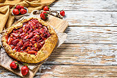 Galette with strawberry and rhubarb. Homemade tart, tarte.  White wooden background. Top view. Copy space