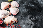 Fresh chicken thigh, organic poultry meat. Black background. Top view. Copy space
