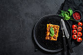Piece of tasty hot lasagna. Traditional italian food. Black background. Top view. Space for text