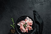 Pork bacon on a black plate. Farm organic meat. Black background. Top view. Space for text