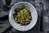Wok. Soba stir fry noodles with beef and vegetables. Black background. Top view