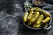 Marinated pickled cucumbers with herbs and spices. Black background. Top view. Copy space