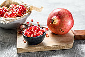 Ripe pomegranate and seeds on a wooden cutting Board. Organic fruit. Gray background. Top view