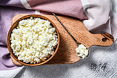 Fresh Cottage cheese in a wooden bowl on cutting board.  Gray background. Top view