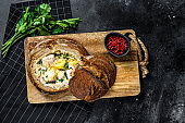 Finnish Creamy fish soup with salmon, trout, potatoes served in bread. Black background, top view, space for text