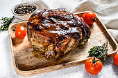 Roasted pork neck meat with spices on cutting board. Gray background. Top view