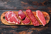 Raw prime black angus beef steaks fillet Mignon, rib eye or cowboy, Striploin or new york, skirt or machete. Wooden dark background. Top view
