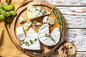 Assorted cheeses on a round wooden cutting Board. Camembert, brie and blue cheese with grapes. White wooden background. Top view