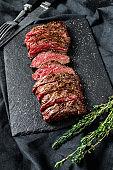 Grilled roasting rare sliced top blade, Denver steak. Marble meat beef. Black background. Top view