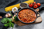 Italian food ingredients for Spaghetti Bolognese. Raw pasta, Basil, ground beef, tomatoes. Gray background. Top view