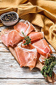 Prosciutto crudo on a cutting board, cured ham. White wooden background. Top view